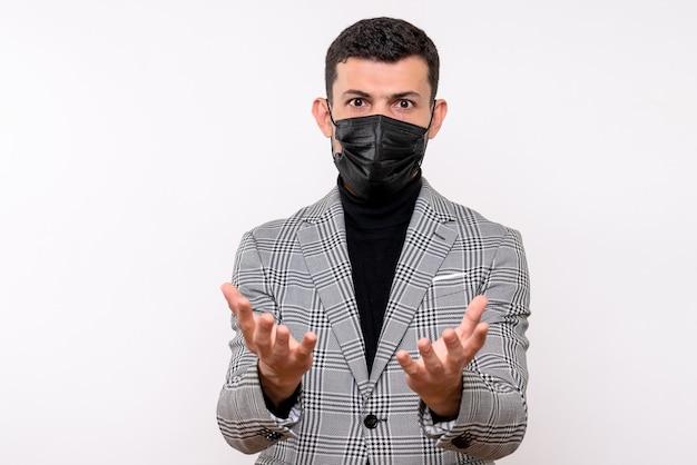 Vista frontale serio giovane uomo con maschera nera in piedi su sfondo bianco isolato