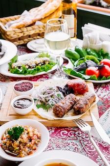 Вид спереди подается столовый люля-кебаб на лаваше с луком и помидорами