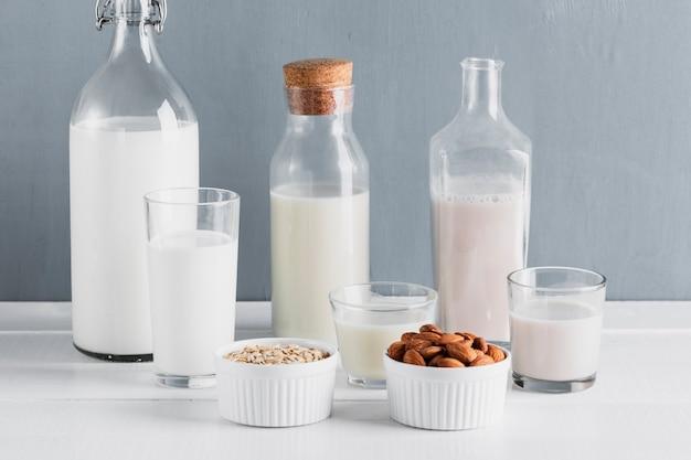 Vista frontale set di bottiglie di latte e bicchieri con farina d'avena e mandorle