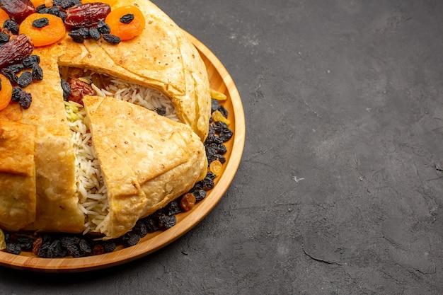 Vista frontale shakh plov delizioso pasto di riso cucinato all'interno di pasta rotonda con uvetta su uno spazio grigio scuro