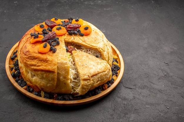 Front view shakh plov delicious rice meal cooked inside round dough with raisins on grey space