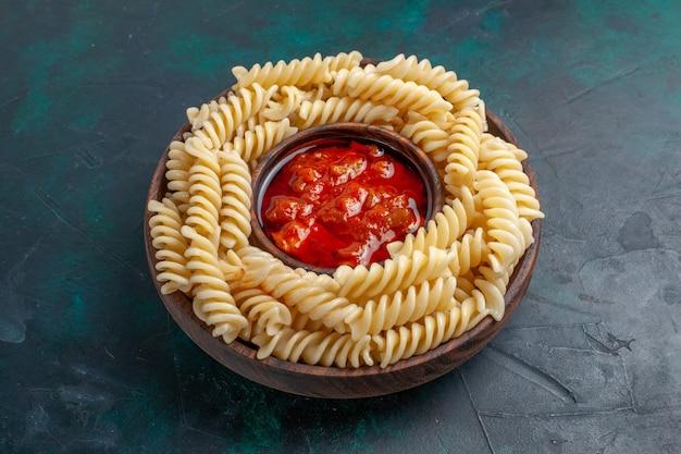 Vista frontale a forma di pasta italiana con salsa di pomodoro su superficie blu scuro