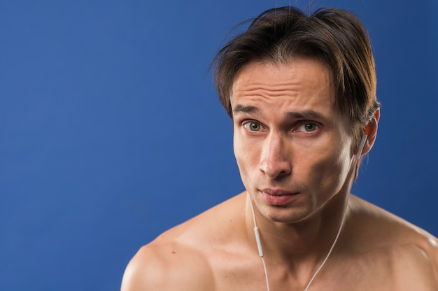 Front view of shirtless athlete with headphones and copy space