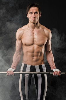 Front view of shirtless athletic man holding weight set