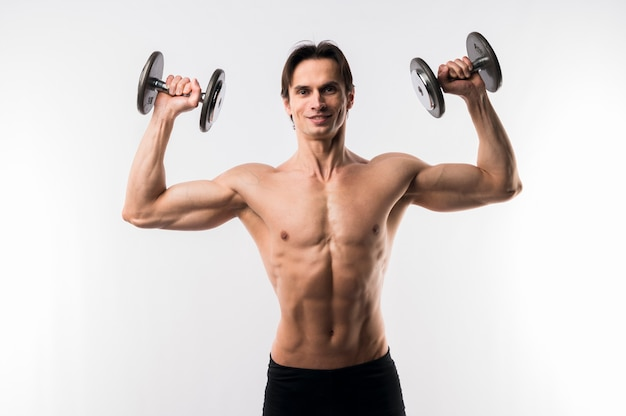 Front view of shirtless athletic man with weights