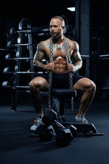 Front view of shirtless bodybuilder sitting on bench with dumbbells on floor.