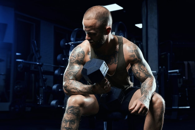 Front view of shirtless bodybuilder training biceps with dumbbell on bench. close up of muscular sportsman with perfect body posing in gym in dark atmosphere. concept of bodybuilding.