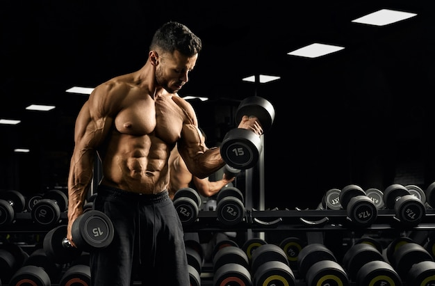 Front view of shirtless bodybuilder training biceps with weights near stand with dumbbells.