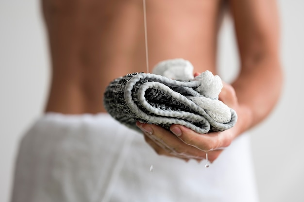 Front view of shirtless defocused man holding washcloth