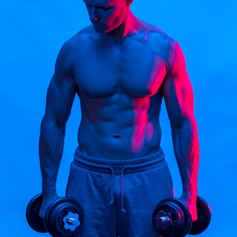 Front view of shirtless fit man holding weights