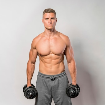 Front view of shirtless fit man posing while holding weights