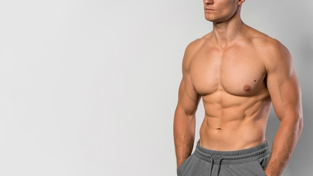 Front view of shirtless fit man posing with copy space
