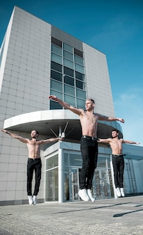 Front view of shirtless hip hop performers dancing routine outside