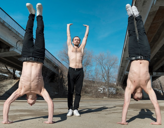 Front view of shirtless hip hop performers posing while practicing dance