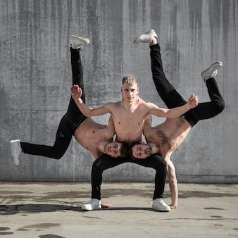 Vista frontale degli artisti hip-hop senza camicia che praticano la posa di ballo