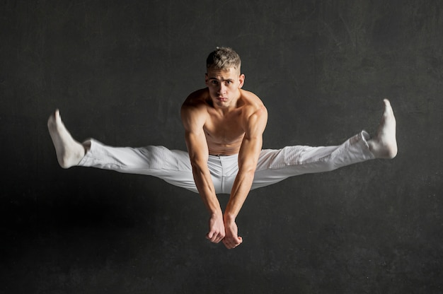 Front view of shirtless male dancer posing in mid-air