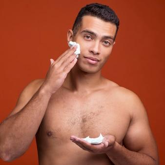 Front view of shirtless man applying shaving foam