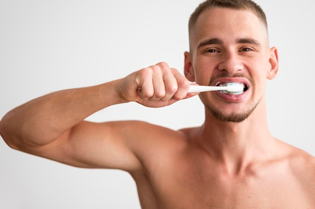 Front view of shirtless man brushing his teeth