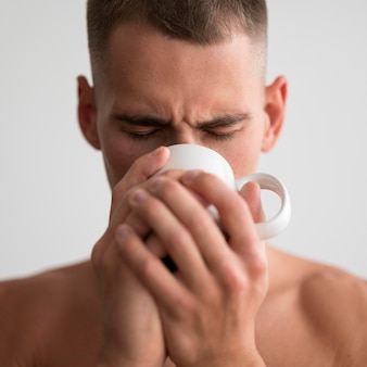 Front view of shirtless man drinking coffee in the morning