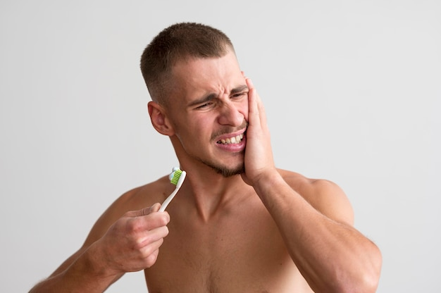 Front view of shirtless man having a toothache and holding toothbrush