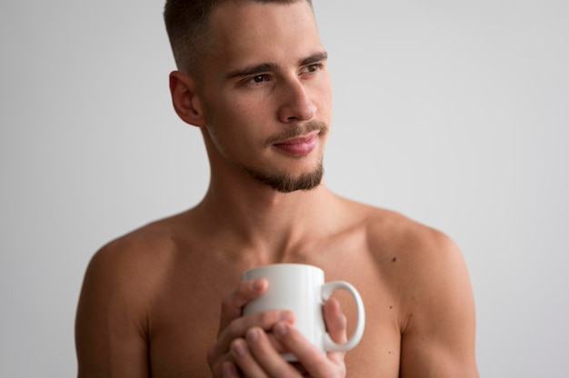 Front view of shirtless man holding coffee mug in the morning