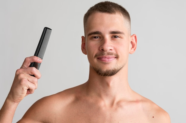 Front view of shirtless man holding a comb