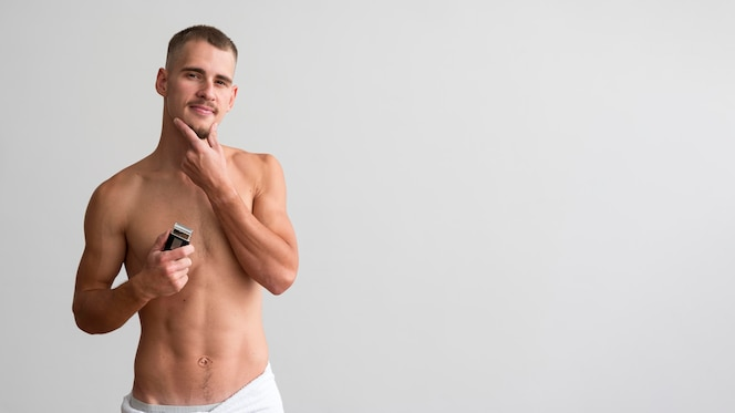 Front view of shirtless man holding electric shaver with copy space