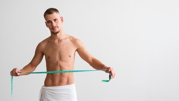 Front view of shirtless man holding measuring tape with copy space