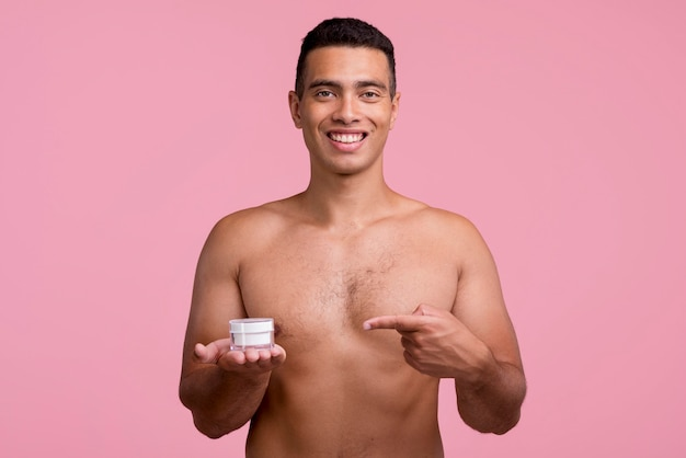Front view of shirtless man holding and pointing at face cream