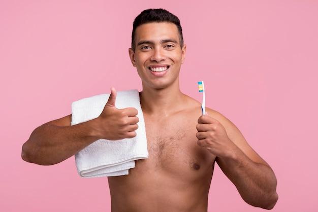 Vista frontale dell'uomo senza camicia che tiene lo spazzolino da denti e che dà i pollici in su