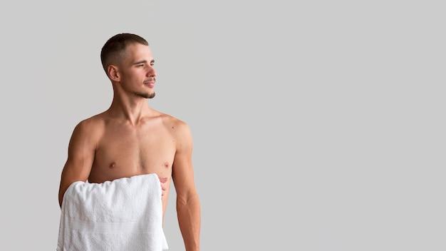 Vista frontale dell'uomo senza camicia che tiene l'asciugamano con lo spazio della copia