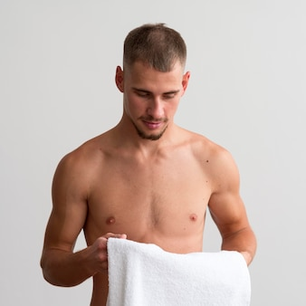 Front view of shirtless man holding towel