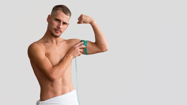 Front view of shirtless man measuring his bicep with tape