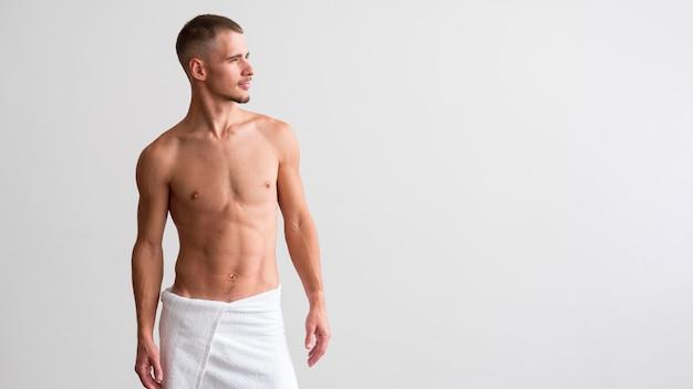 Vista frontale dell'uomo senza camicia che posa con lo spazio della copia
