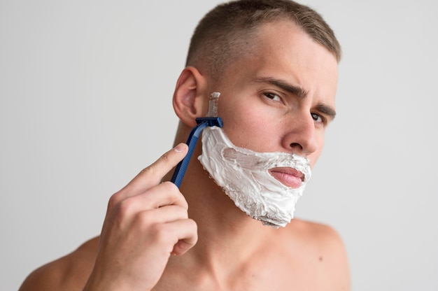 Front view of shirtless man shaving his beard