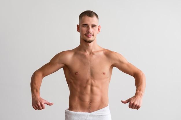 Vista frontale dell'uomo senza camicia che mostra il suo corpo