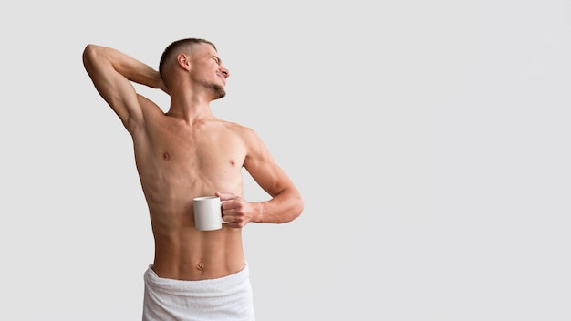 Front view of shirtless man stretching in the morning with copy space
