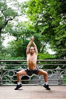 Front view of shirtless man stretching
