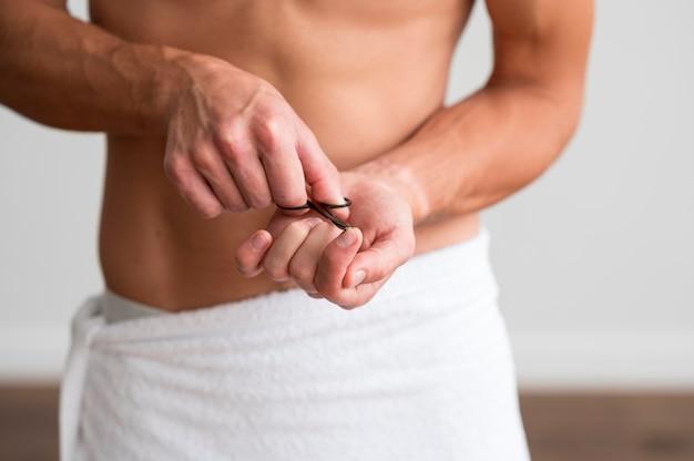 Vista frontale dell'uomo a torso nudo in un asciugamano usando le forbici sulle unghie