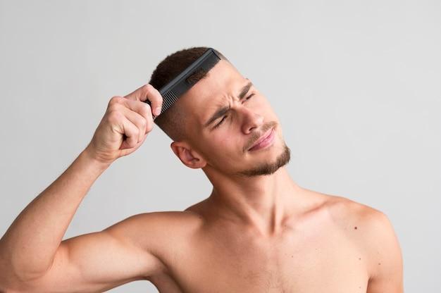 Vista frontale dell'uomo senza camicia che usando un pettine