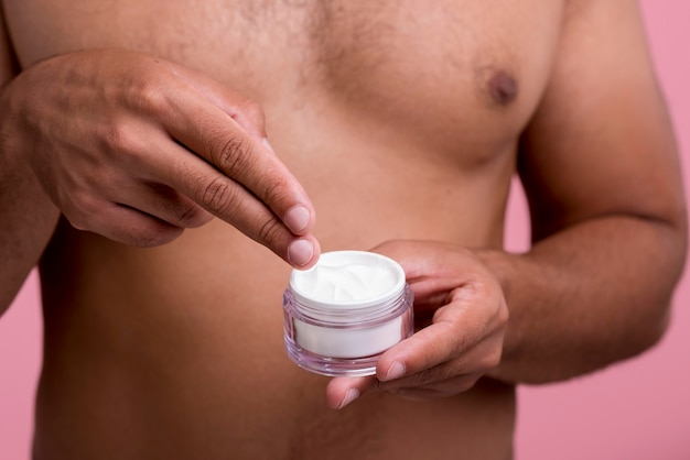 Front view of shirtless man using face cream