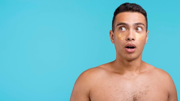 Front view of shirtless man with eye patches and copy space