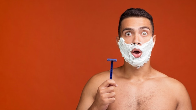 Front view of shirtless man with shaving foam on his face holding razor