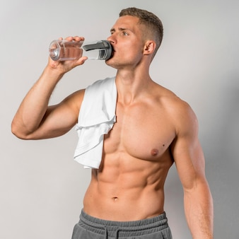 Front view of shirtless man with towel drinking water