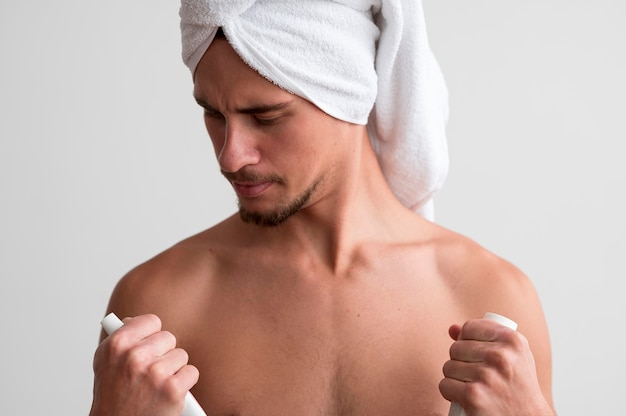 Front view of shirtless man with towel on his head looking at care products