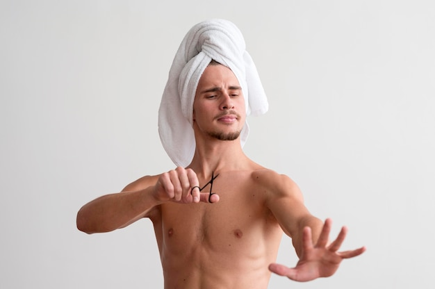 Front view of shirtless man with towel on his head looking at his fingernails