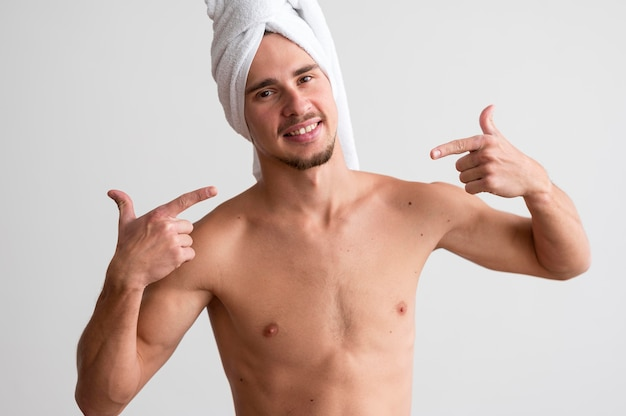 Front view of shirtless man with towel on his head pointing to himself