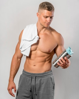 Front view of shirtless man with towel and water bottle