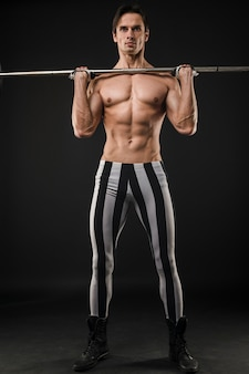 Front view of shirtless muscled man lifting weights