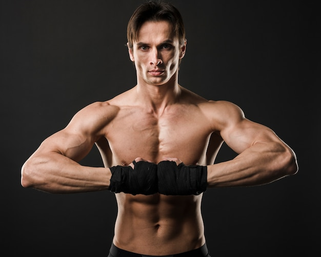 Front view of shirtless muscled man posing with boxing gloves
